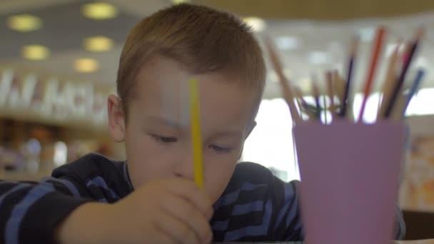 U stolu sedí malý chlapec a kreslí pastelkami