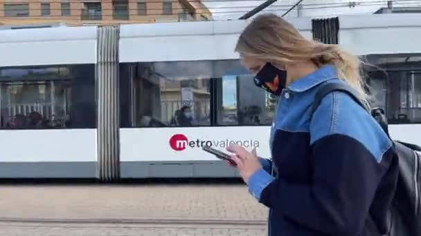 Woman citizen with mobile walking in the street with tram passing by