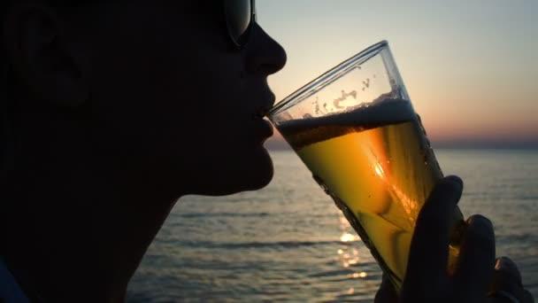Žena sedí na pláži při západu slunce
