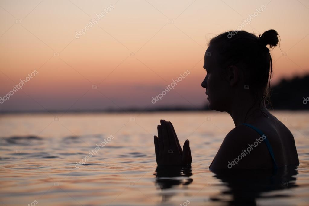 Woman in water during pray or meditation