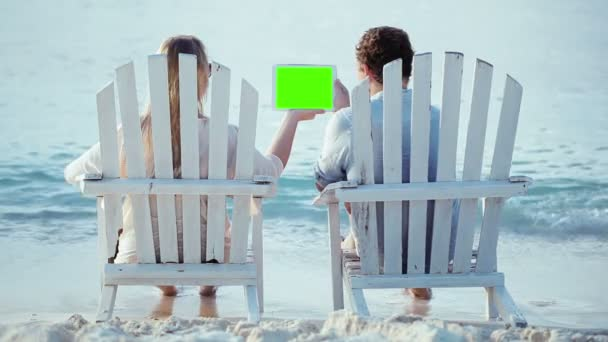 Woman and man sitting on the beach and looking at pad with green screen
