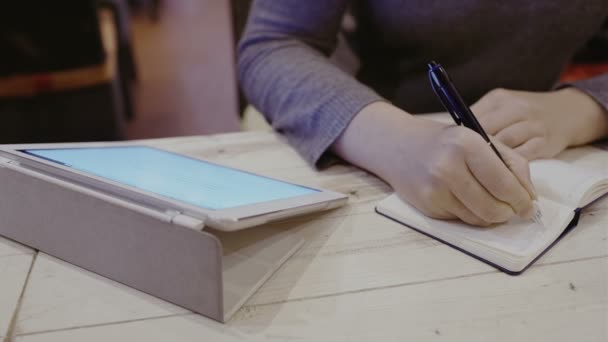 Woman taking notes in notebook, touch pad nearby