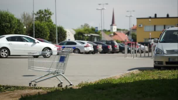 Timelapse of traffic on parking zone with empty shopping cart