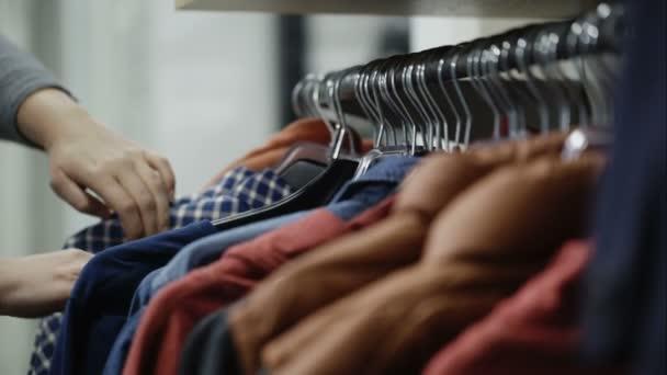 Žena vypadá přes bundy a košile v nákupní centrum