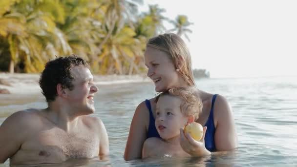 Rodina ze tří relaxační v mořské vodě v tropech