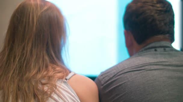 Fiatal férfi és nő otthon tévénézés