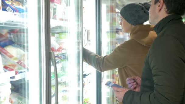 Mladí lidé brát produkt v lednici sekce