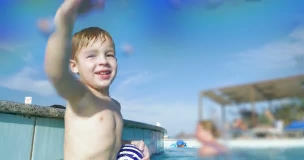 Happy child in swimming pool splashing water