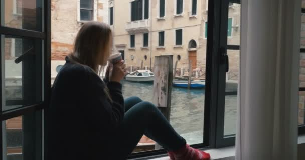 Woman drinking coffee and looking at Venice view