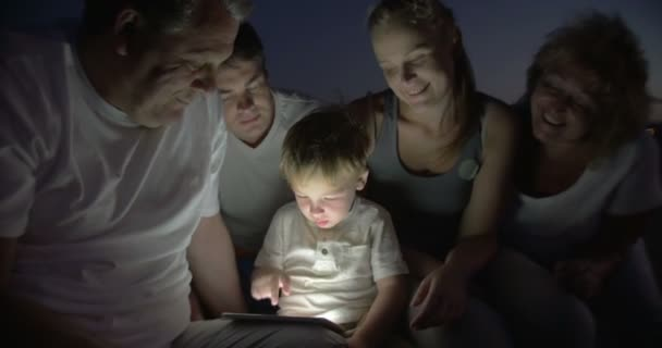 Big Family Watching Bedtime Story on Tablet PC