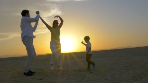 Happy family of three dancing on the beach at sunset