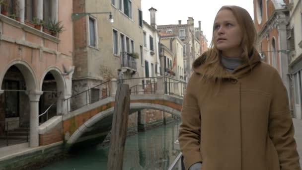 Woman having coffee while walking in Venice