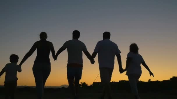 Big friendly family walking outdoor at sunset