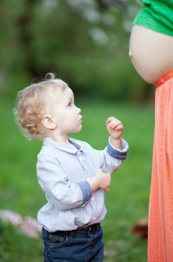 Cute little boy looking at pregnant moms belly