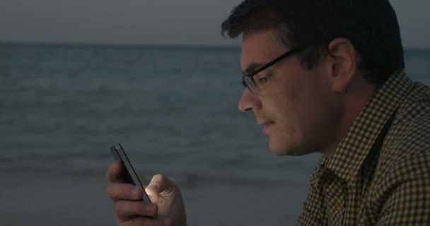 Young man communicating on cell by the sea