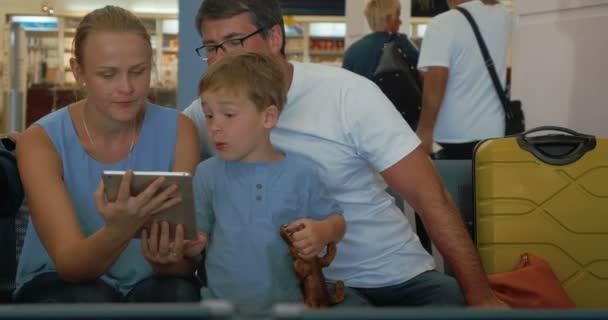 Rodiče a děti používající digitální tablet na letišti