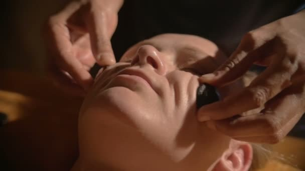 Relaxing facial massage with hot stones in beauty spa