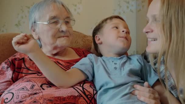 Little boy expressing love to mother and grandmother with kisses
