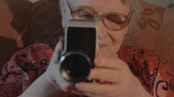 Senior woman filming with retro video camera