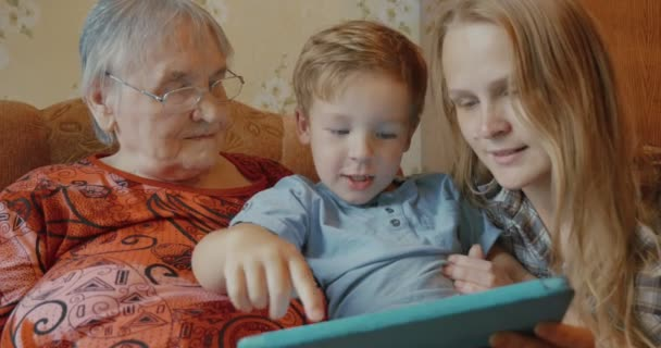Family uses tablet sitting on the sofa