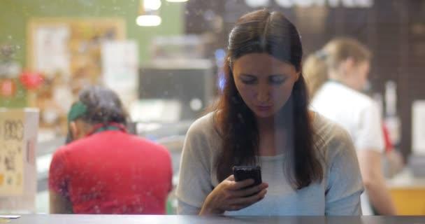 Mladá brunetka pomocí smartphone v kavárně