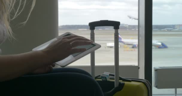 Woman waiting for the flight with tablet PC