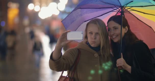 Women making funny selfie in evening rainy city