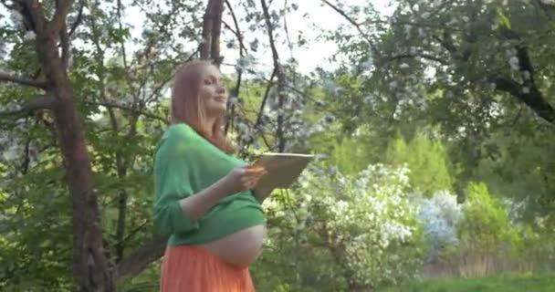 Těhotná žena s procházku s podložkou v parku