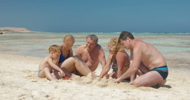 Big family building sand castle together