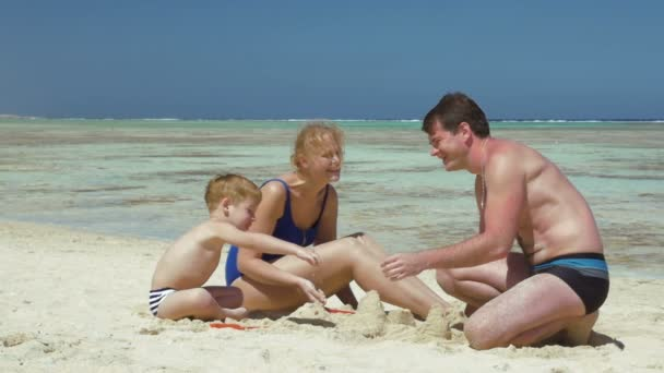 Parents and son playing with sand on the beach
