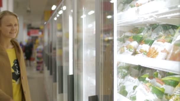 Woman taking frozen product in the shop fridge