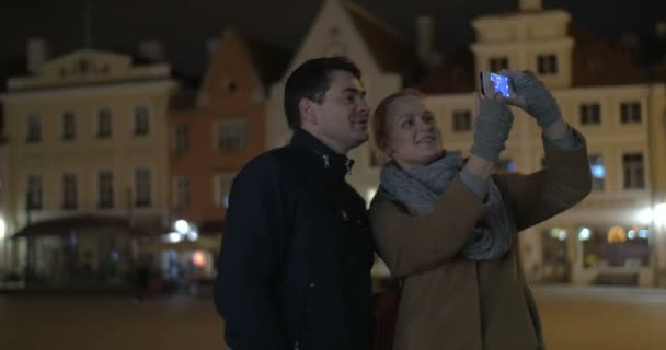 Happy couple making phone selfie in the evening street