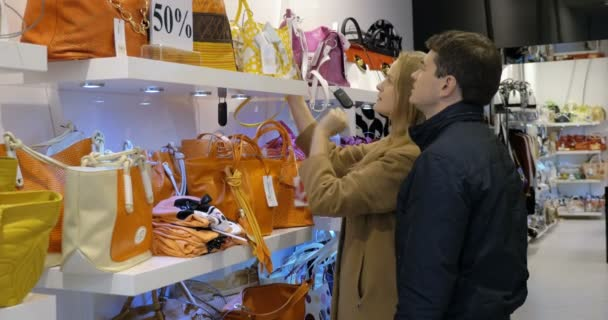Couple choosing a handbag in the shop
