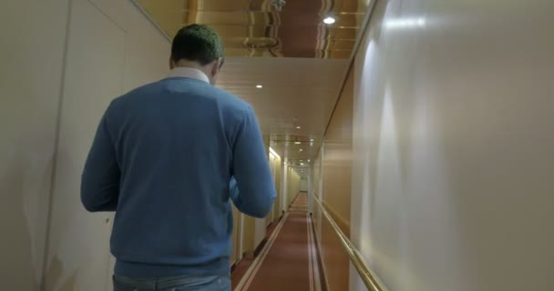 Adult Man Walking Along A Corridor Of Ocean Cruise Ship