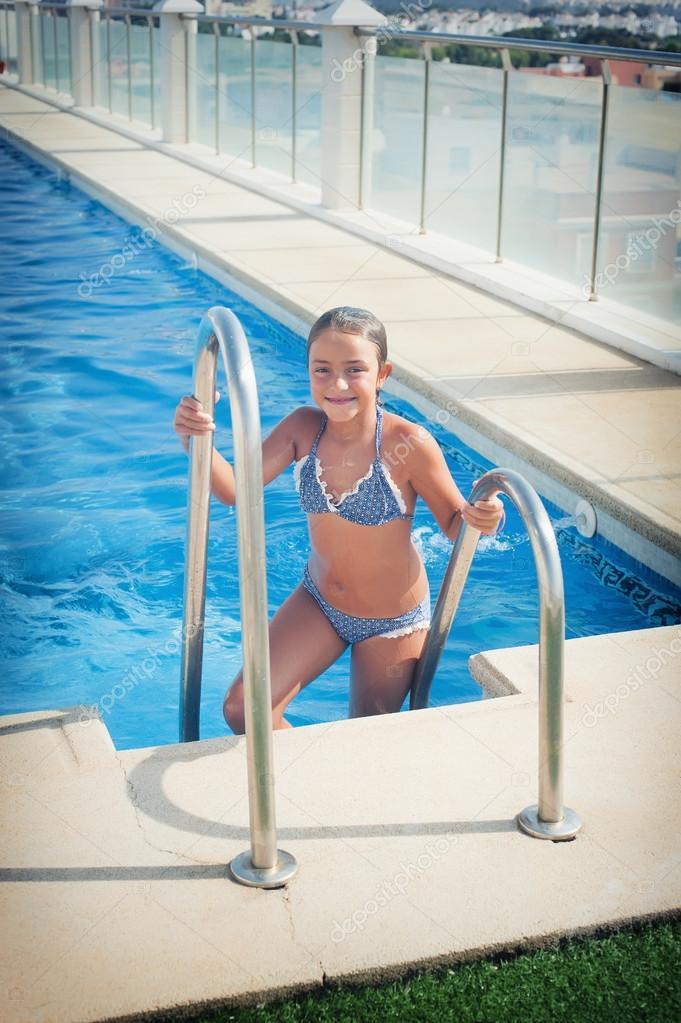 Jovencita guapa en traje de baño al borde de la piscina y ...