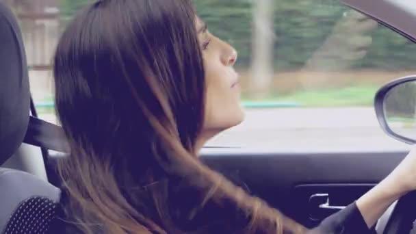 Nádherná mladá dáma sedící v autě baví tanec s dlouhými vlasy
