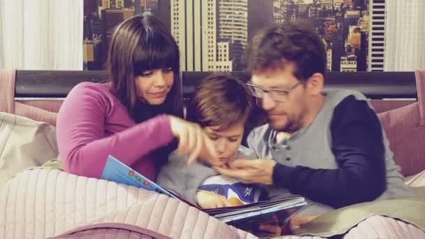 Šťastná rodina v posteli baví čtení knihy hrát s klukem