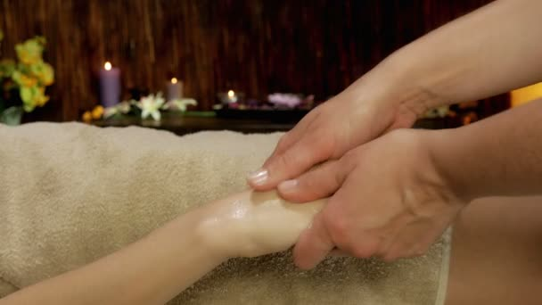 Closeup of hand and fingers massage in spa with candles 4K