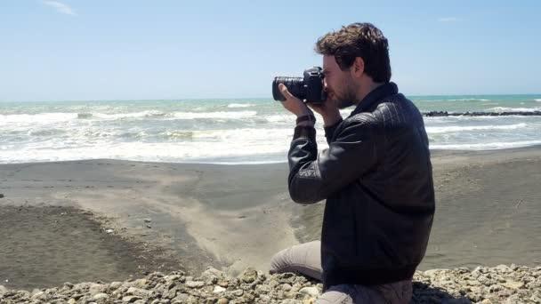 Handome člověk fotí s profesionální kamerou na pobřeží oceánu