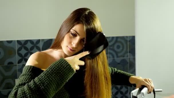 Krásná žena v koupelně rovnání dlouhé vlasy s železem