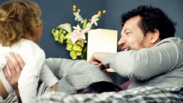 Šťastná rodina hraje v posteli