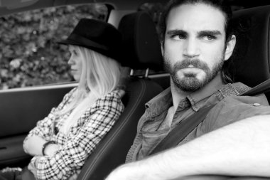Angry young couple in car after breaking up. Black and withe
