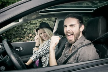Cars - cool hipster couple driving in new car screaming happy, looking at camera