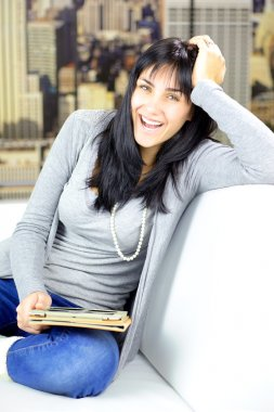 Happy smiling young woman at home in city holding tablet