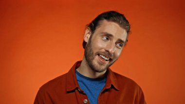 Joyful and bearded man smiling while looking away on orange stock vector
