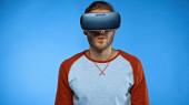 vousatý muž ve virtuální realitě sluchátka na modrém pozadí