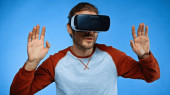 young man in virtual reality headset gesturing on blue
