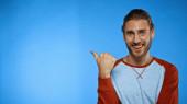 radostný muž ukazuje palcem na modrou