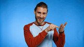 excited young man pointing with finger at hand while looking at camera on blue