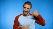 positive young man showing call me gesture while looking at camera on blue